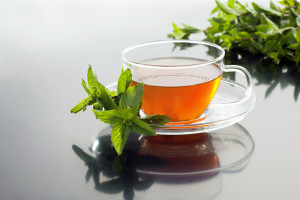 Cup with green tea and fresh mint leaves on grey background